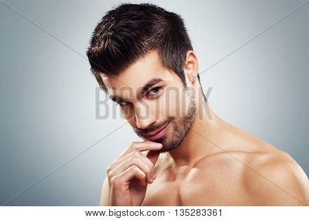 Man's beauty portrait in studio on gray background