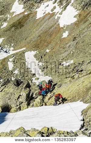 High Tatras Slovakia - June 18 2016: Mountain guide takes steps in the snow for a group of clients which leads couloir in the mountains.