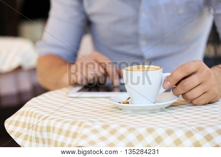 Businessman drinking coffee and using tablet in cafe