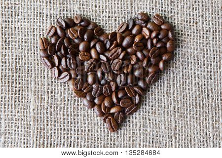 Burlap texture with coffee beans heart shape background. Sack cloth and coffee love sign. Natural sackcloth canvas background with heart and copy space. Seeds at hessian textile