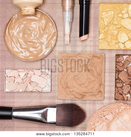 Cream-to-powder and liquid foundation, correctors, shimmer powder golden color, crushed compact powder, bronzer with flat makeup brush and cosmetic sponge on plaid background