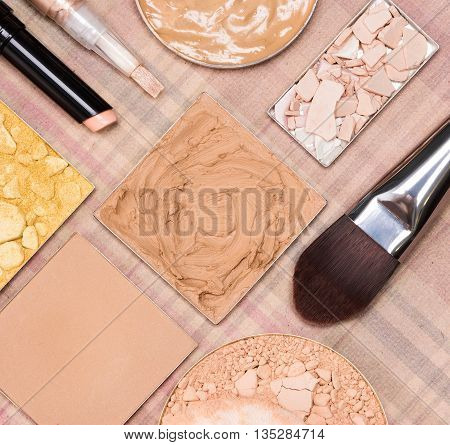 Basic makeup products to create beautiful skin tone and complexion. Correctors, foundation, powder with flat brush and cosmetic sponge on plaid background