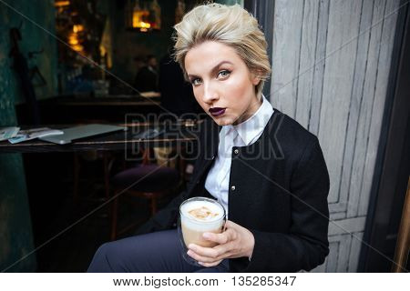 Close-up portrait of a stylish young woman blogger looking at camera and holding cup of coffee