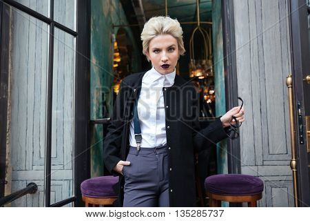 Close-up portrait of a stylish young woman blogger looking at camera