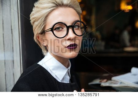 Close-up portrait of a beautiful girl wearing glasses and sitting in cafe