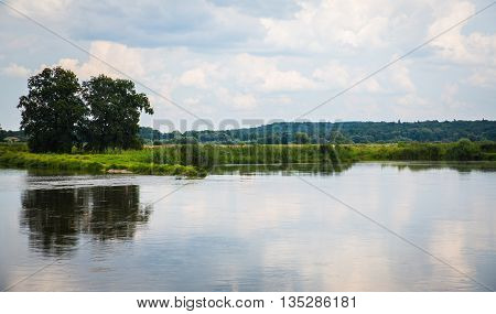 Beautiful wild nature park, forest. River or lake with mirror reflections and clear water on sunny day. Amazing wilderness nature landscape panorama. Quiet river in surroundings greenery in summer.