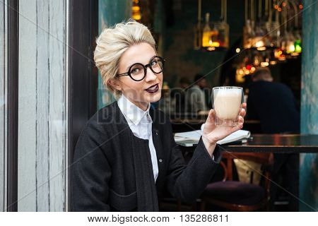 Portrait of a smiling stylish girl holding cup of coffee in cafe outdoors