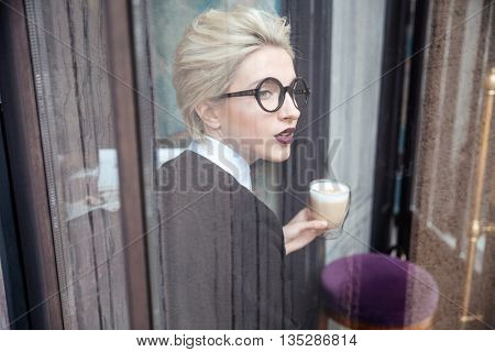 Portrait of a stylish young woman with cup of coffee sitting in cafe