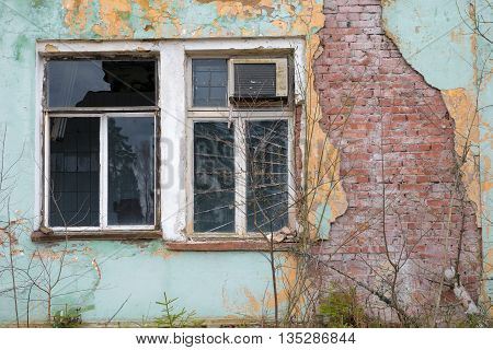 Old evicted and destroyed house with a ruined wall and broken window
