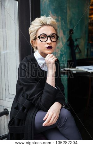 Portrait of stylish beautiful blonde woman sitting in cafe alone