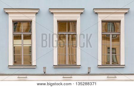 Three windows in a row on facade of urban office building front view St. Petersburg Russia