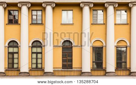 Several windows and columns in a row on facade of urban apartment building front view St. Petersburg Russia