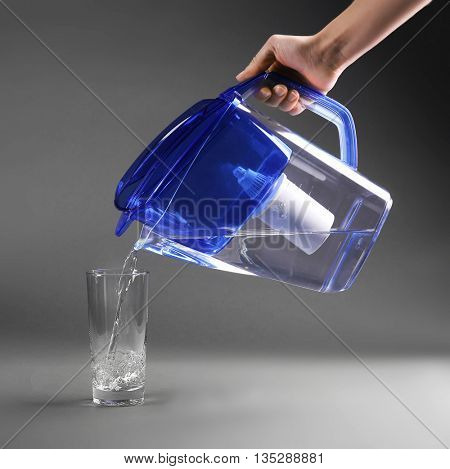 Female hand pouring water into glass on grey background
