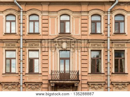 Several windows in a row nd balcony on facade of urban apartment building front view St. Petersburg Russia