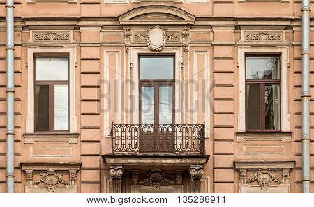 Three windows in a row nd balcony on facade of urban apartment building front view St. Petersburg Russia