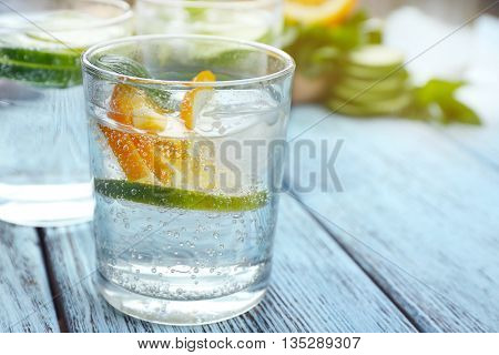 Infused lime water with orange on wooden background