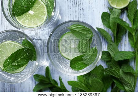 Infused lime water with mint on wooden background