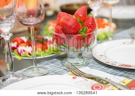 Glassware filled with strawberries on a table during dinner