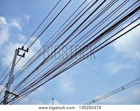 Electric pole connect to the high voltage electric wires on blue sky background.