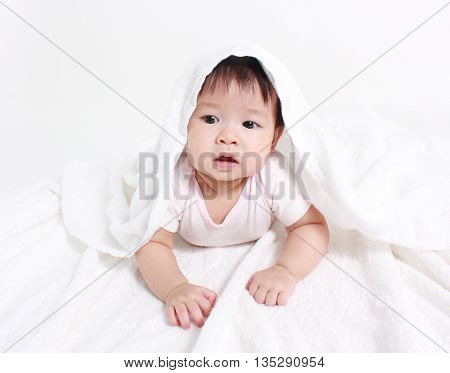 Portrait of smiling baby  under a white blanket/towel
