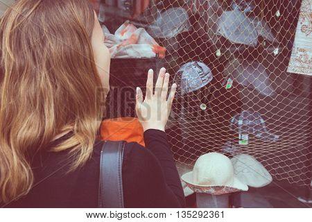 Attractive brunette window shopping. Rear view of a shopper.