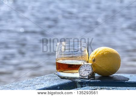 Tumbler of whiskey and lemon with a watch on shore of lake