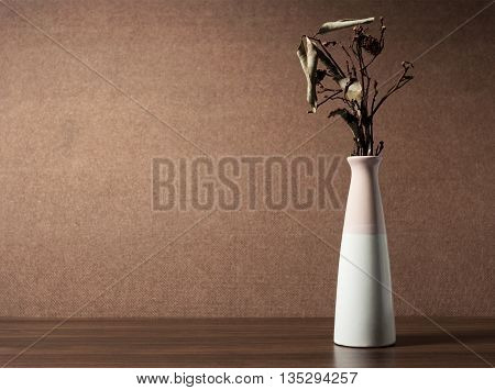 Leaf and branch of flower in vase on wooden table, Still life and low key tone