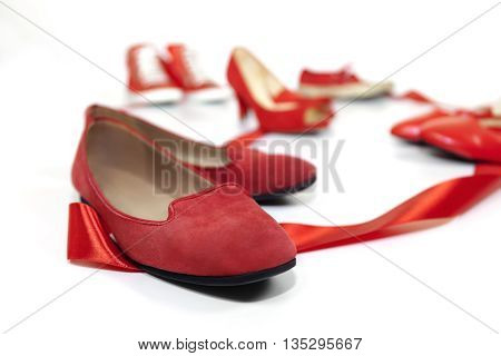 Red shoes women of various models are based on a white floor and are joined by a red ribbon which is the common thread that unites them: violence against women symbolized by red shoes.