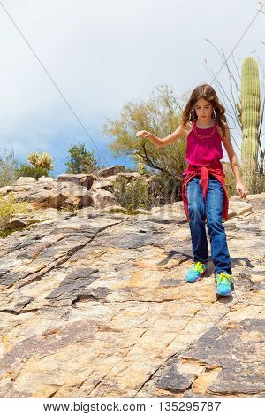 A young girl hiking goes down a rocky incline in the desert with a saguaro cactus in the background.