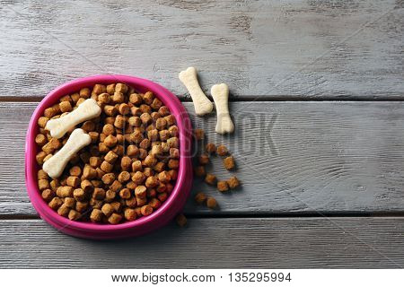Dog food in pink plastic bowl on gray wooden background