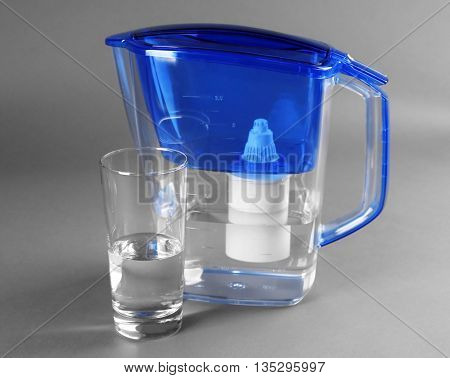 Filter and glass of water on grey background