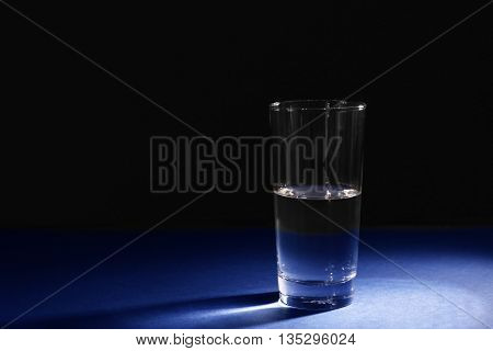 Glass of pure water on dark background