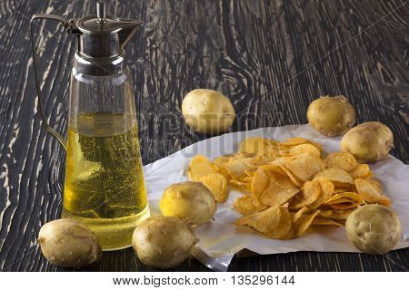 Potato chips, raw potato and jug of an oil on wooden background.