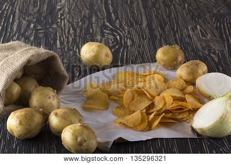 Potato chips, raw potato and onion on wooden background.