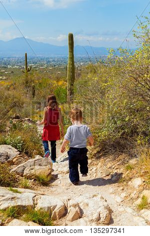 A young girl leads her little brother down a rocky trail in an Arizona desert overlooking Tucson.