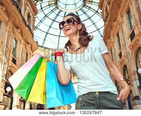 Discover most unexpected trends in Milan. Smiling fashion woman in eyeglasses with colorful shopping bags in Galleria Vittorio Emanuele II looking into the distance
