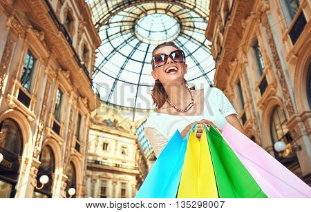 Discover most unexpected trends in Milan. Happy fashion woman in eyeglasses with colorful shopping bags in Galleria Vittorio Emanuele II looking up