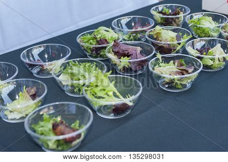 Salad appetizers arranged in small, plastic bowls.