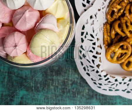 Glass jar with homemade sweet marhmellows, salted cookies in tablecloth, blue background