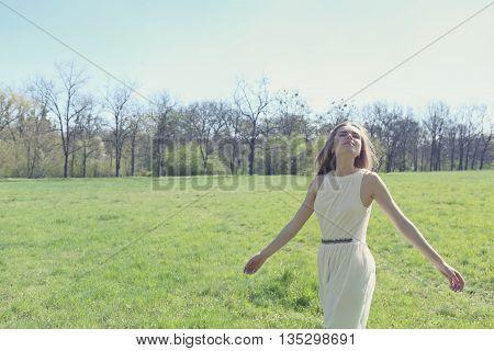 freedom dreamy girl in a summer dress in a meadow