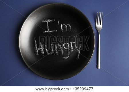 Plate with text I'M HUNGRY on blue background