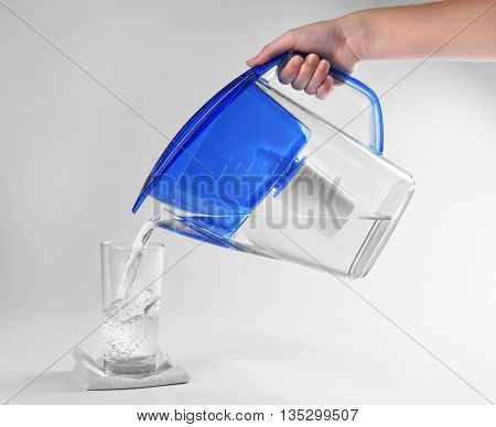 Purified water pouring into glass on white background