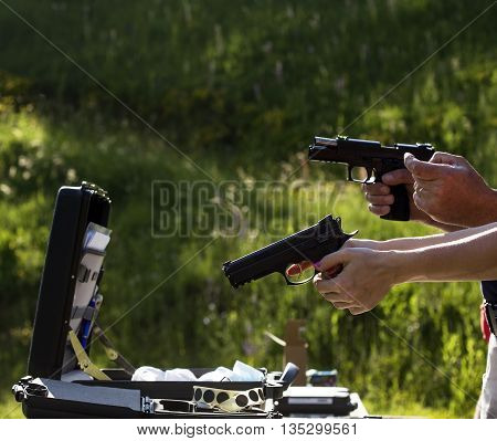 Persons are holding guns and talking about technique.