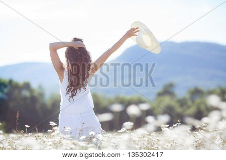 Slender young brunette woman with long curly hair, wearing a white summer dress, standing in a field among white daisy flowers looking in the direction of the mountain massif, in his raised hand holding a white hat with large fields