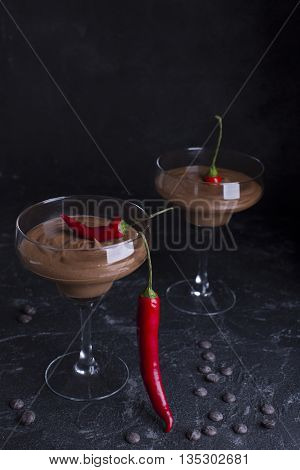 Chocolate mousse in glasses on a dark background with red pepper