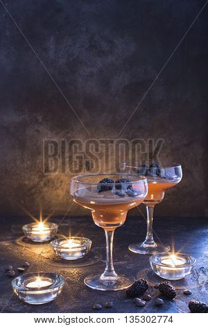 Chocolate mousse in glasses on a dark background with blackberries and candles