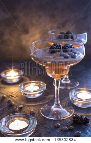 Chocolate mousse in glasses on a dark background with blackberries and candles close-up