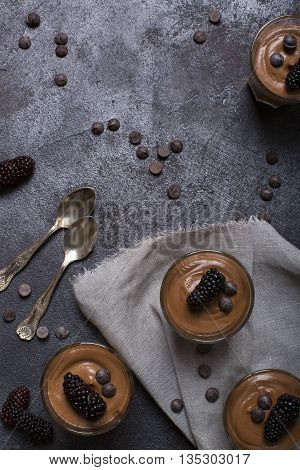 Chocolate mousse in glasses on a dark background with blackberries top view