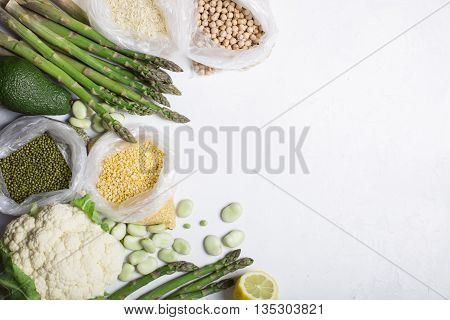 Still life of green and yellow vegetables and cereals on a light background copy Space