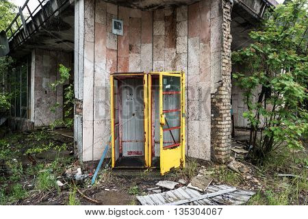 rusty yellow telephote booth in abandoned Pripyat, Chernobyl, Ukraine